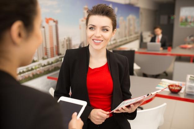 Empresária sorridente, falando com o colega