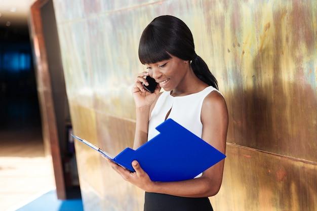 Empresária sorridente lendo jornais e falando ao telefone no escritório