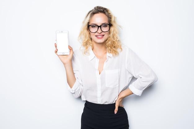 Empresária sorridente mostrando a tela do smartphone em branco sobre parede cinza. vestindo óculos e camisa azul.