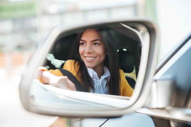 Empresária sorridente no espelho retrovisor do carro