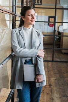 Empresária sorridente pensativa, apoiando-se na parede de vidro e segurando o diário no escritório