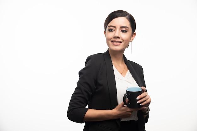 Empresária sorridente segurando copo na parede branca.