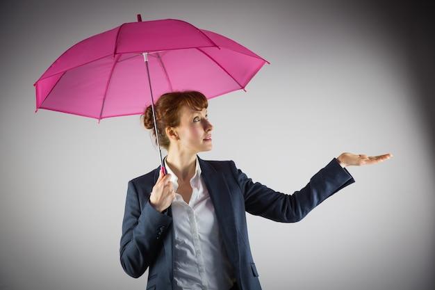 Empresária sorridente segurando guarda-chuva rosa