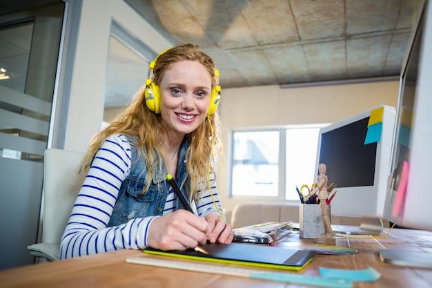 Empresária sorridente sentada em sua mesa e ouvindo música