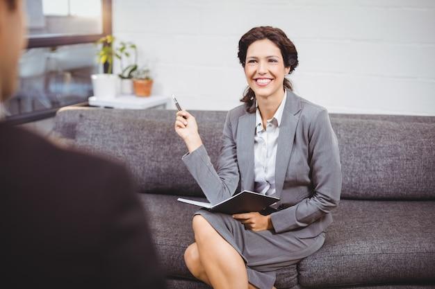 Empresária sorridente, sentado no sofá no escritório