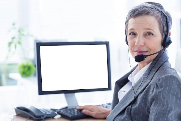 Empresária sorridente telefonando e usando computador