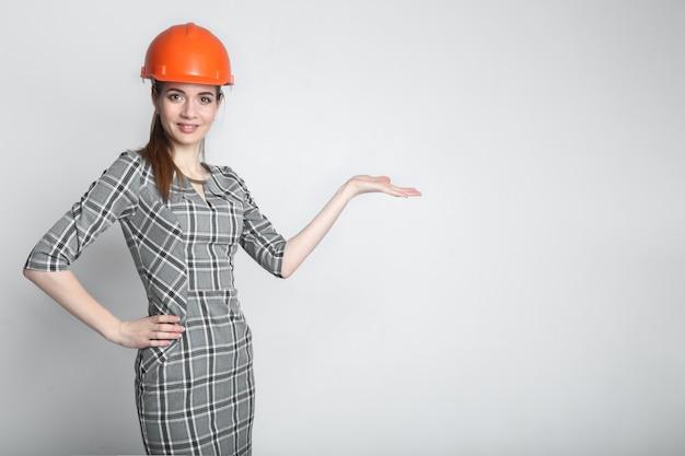 Empresária sorridente usando capacete construtor apontando o dedo no espaço da cópia