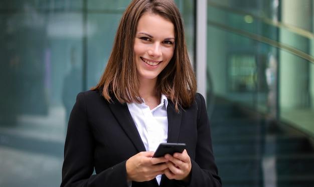 Empresária sorridente usando um smartphone ao ar livre