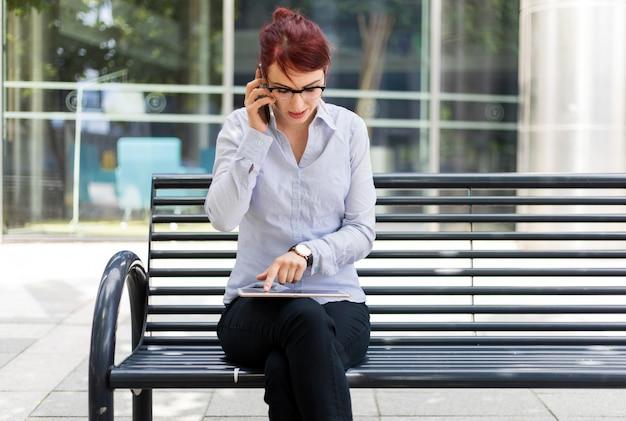 Empresária sorridente usando um tablet digital ao ar livre, enquanto no telefone
