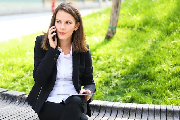 Empresária sorridente usando um tablet digital ao ar livre, sentado num banco e falando ao telefone