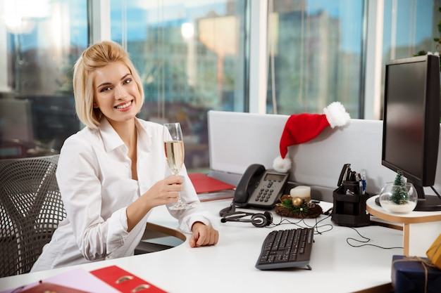 Empresária, sorrindo bebendo champanhe sentado no escritório, no dia de natal.