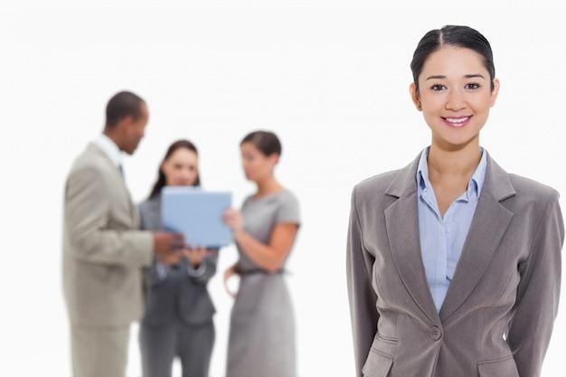 Empresária sorrindo com colegas de trabalho ao fundo