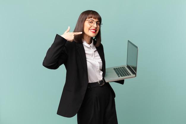 Empresária sorrindo com confiança apontando para o próprio sorriso largo, atitude positiva, relaxada e satisfeita
