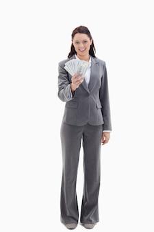 Empresária sorrindo e segurando muitos dólares em notas de banco