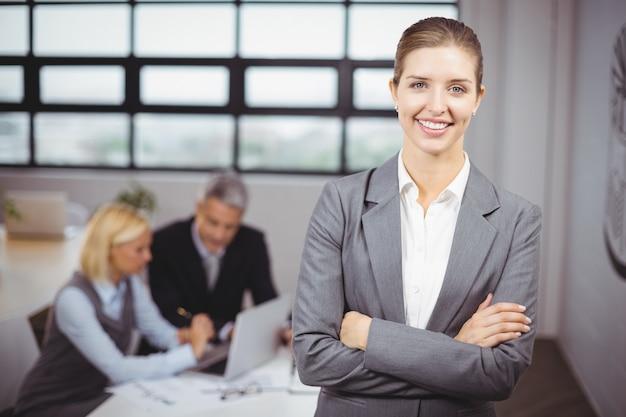 Empresária sorrindo enquanto pessoas de negócios sentado no fundo