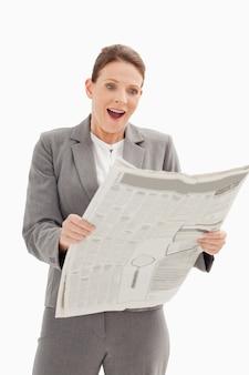 Empresária surpresa em pé lendo o jornal