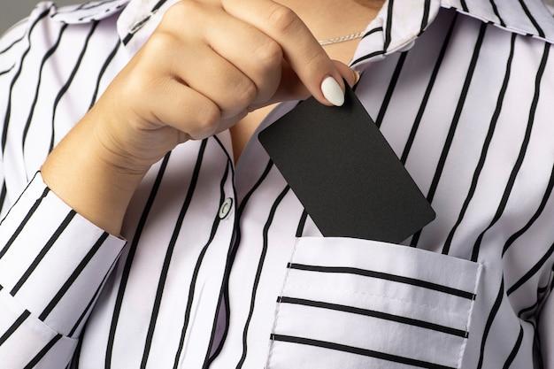 Empresária tira um cartão preto do bolso da blusa.
