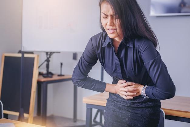 Empresária tocando o estômago doloroso, sofrendo de dor de estômago por causa do período de menstruação.