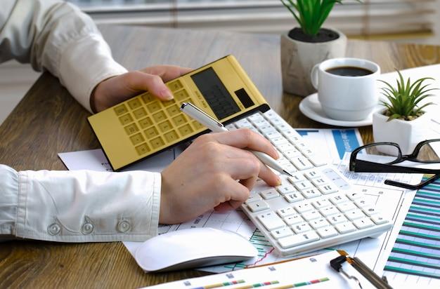 Empresária trabalha com itens para fazer negócios no escritório.