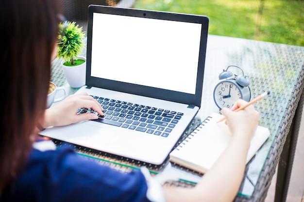 Empresária, trabalhando com o laptop e o smartphone na cafeteria