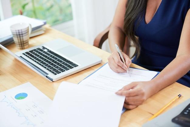 Empresária trabalhando com relatórios, respondendo a e-mails e assinando acordos na mesa do escritório