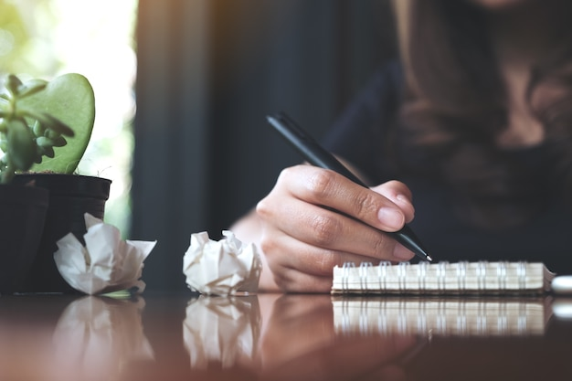 Empresária, trabalhando e escrevendo em um caderno em branco branco com papéis