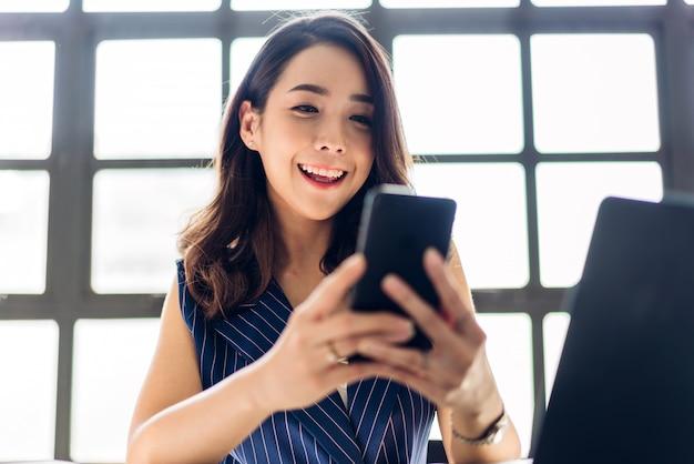 Empresária, trabalhando e usar o smartphone com computador portátil. pessoas de negócios criativas, planejando no loft de trabalho moderno