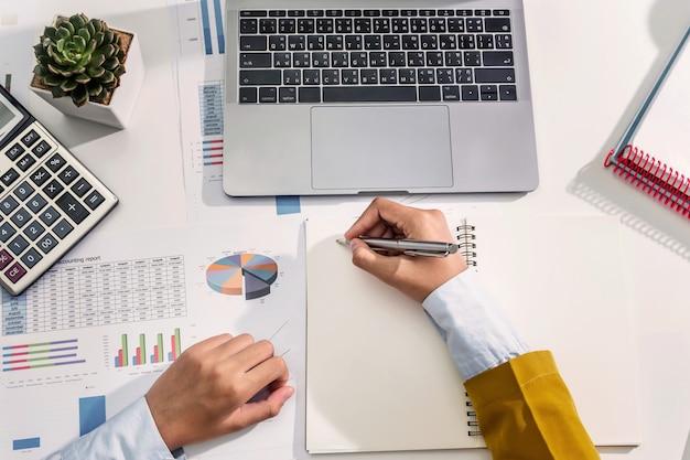 Empresária, trabalhando na mesa usando a calculadora e laptop, analisando a contabilidade financeira