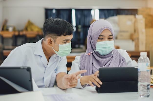 Empresária usando máscara protetora e analisando finanças da empresa