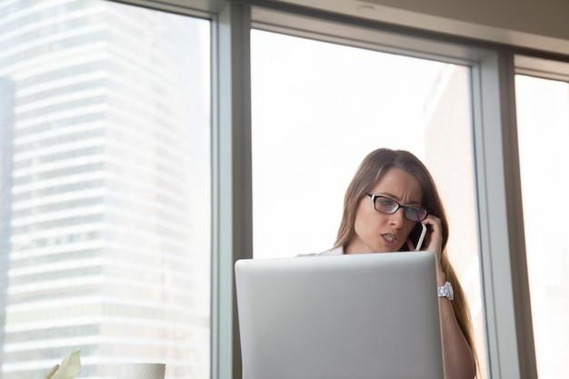 Empresária zangada, falando no celular no local de trabalho, discutindo por celular