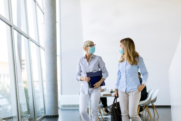 Empresárias andando no escritório e usando máscara como proteção contra vírus