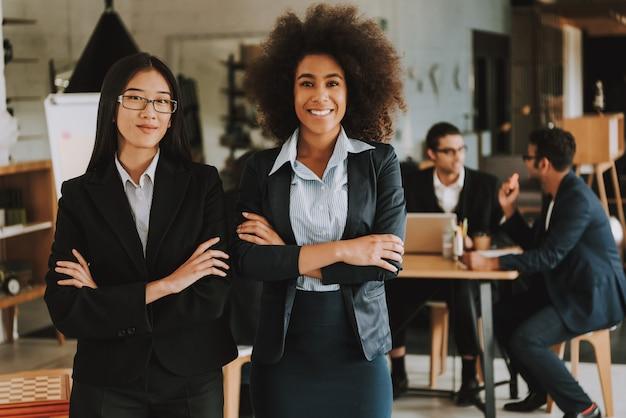 Empresárias asiáticas e afro-americanas com braços cruzados.