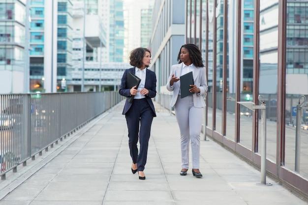 Empresárias, caminhando e conversando na rua