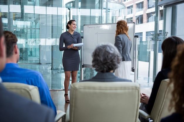 Empresárias discutindo no quadro branco com colegas de trabalho