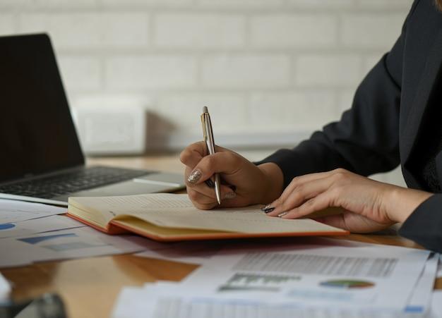 Empresárias estão tomando notas de trabalho sobre a mesa no escritório.