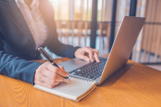 Empresárias estão tomando notas em papel com uma caneta preta, e ela está usando um computador portátil em uma mesa de madeira no escritório.