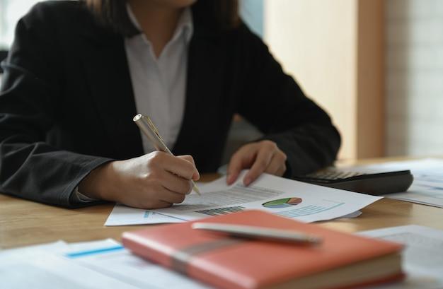 Empresárias estão trabalhando na mesa do escritório. ela apontou o gráfico para analisar.