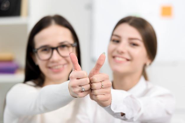 Empresárias jovens borradas, mostrando o polegar para cima o sinal em direção à câmera