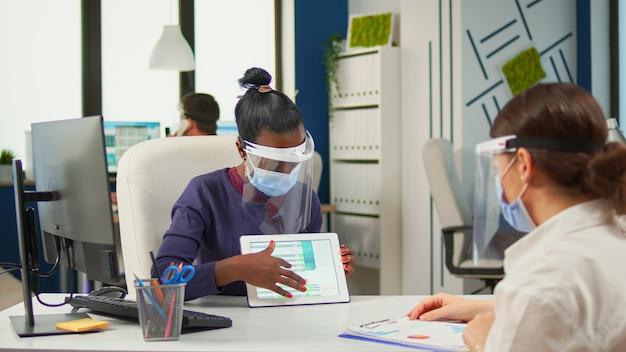 Empresárias multiétnicas discutindo trabalho e usando tablet digital durante reunião usando máscara de proteção respeitando a distância social. grupo de diversos empresários trabalhando em segundo plano.