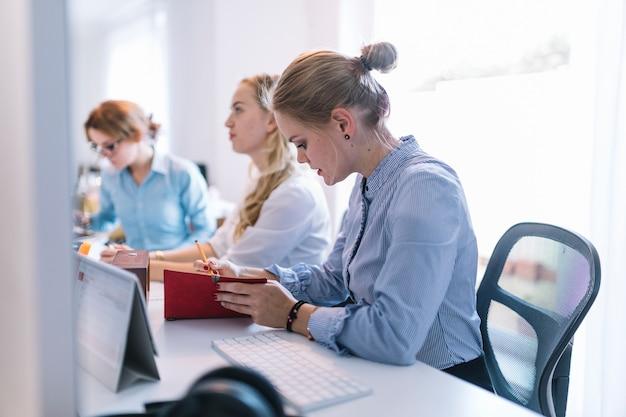 Empresárias, sentado em uma fileira, trabalhando no escritório