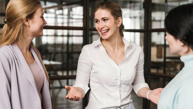 Empresárias sorridentes conversando em ambientes fechados