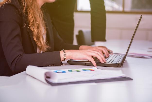 Empresárias trabalhando em laptop com colegas
