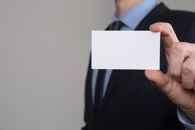 Empresário, a mão do homem de negócios segura apresentando cartão de visita - close-up filmado em fundo cinza. mostre um pedaço de papel em branco. cartão de visita em papel.