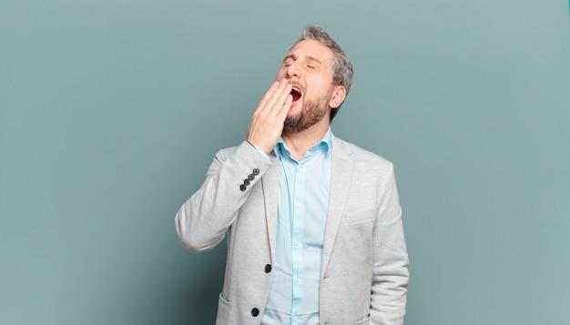 Empresário adulto bocejando preguiçosamente no início da manhã, acordando e parecendo sonolento