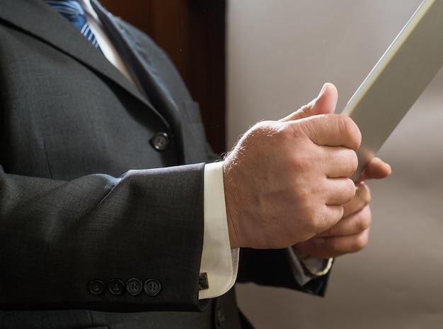 Empresário adulto em pé de terno e usar tablet
