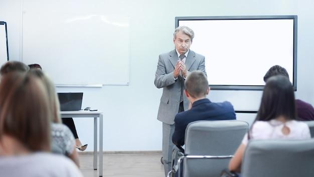 Empresário adulto faz um relatório para os funcionários em uma reunião no escritório.