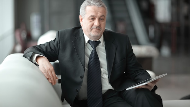 Empresário adulto olhando para a tela do tablet digital.