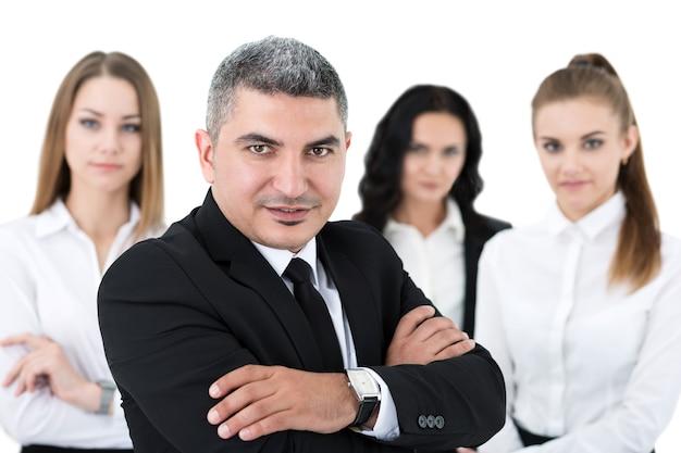 Empresário adulto sorridente em pé na frente de seus colegas com os braços cruzados no peito. grupo de equipe de executivos.