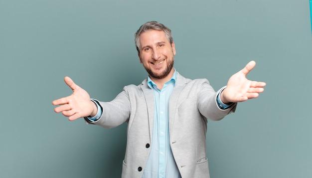 Empresário adulto sorrindo alegremente dando um abraço caloroso, amigável e afetuoso de boas-vindas, sentindo-se feliz e adorável
