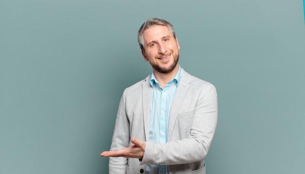 Empresário adulto sorrindo alegremente, sentindo-se feliz e mostrando um conceito no espaço da cópia com a palma da mão